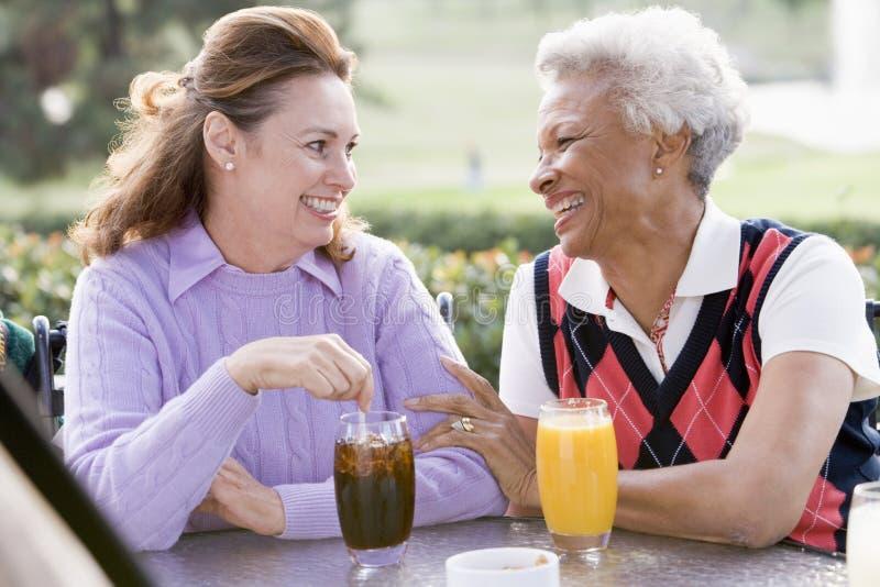 Zwei weibliche Freunde, die ein Getränk durch ein Golf C genießen stockfotos