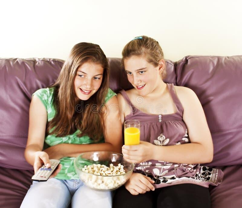Zwei weibliche Freunde, die televison überwachen stockbilder