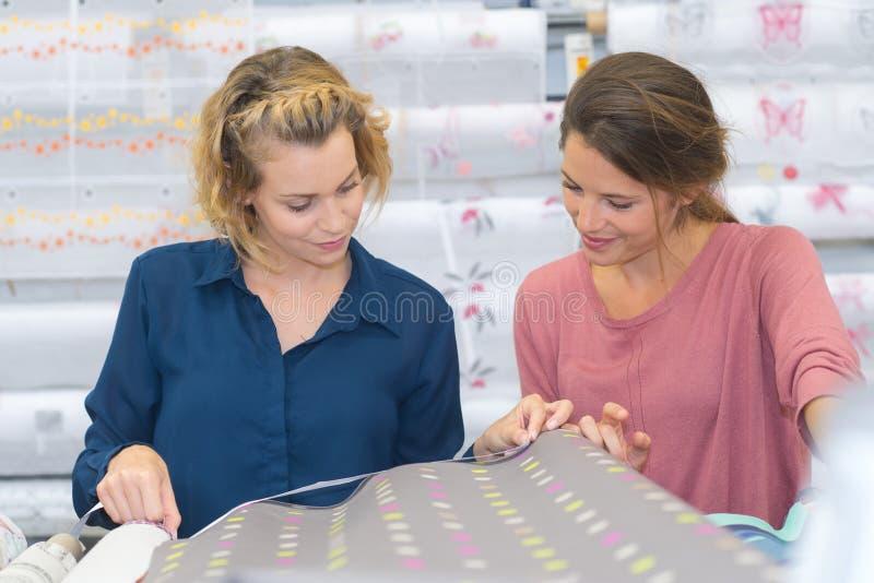 Zwei weibliche Kunden, die Gewebe im Speicher vorwählen lizenzfreies stockbild
