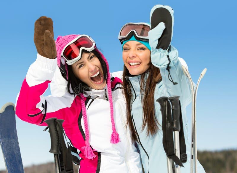 Zwei weibliche Skifahrerfreunde mit den Händen oben lizenzfreies stockfoto