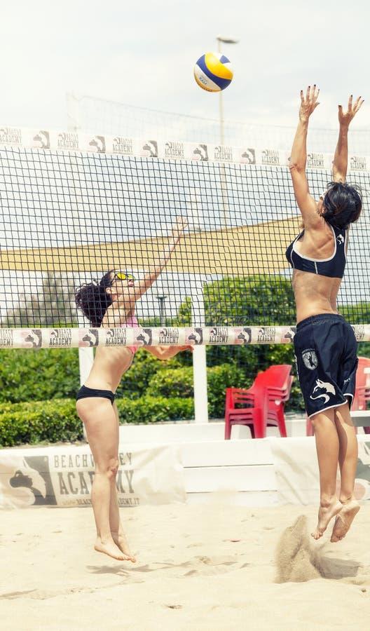 Zwei weibliche Strandvolleyballspieler Angriff und Verteidigung stockfoto