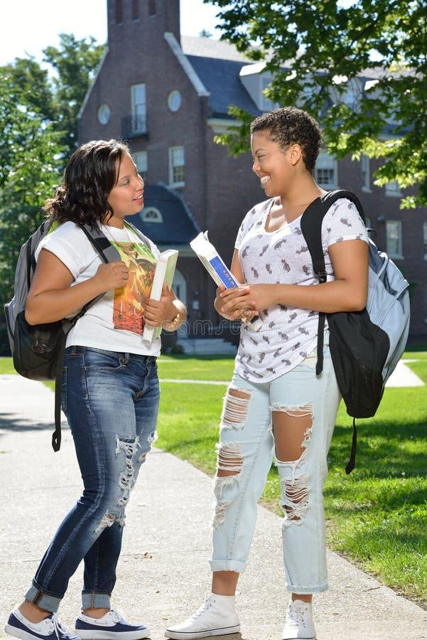 Zwei weibliche Studenten auf dem Campus mit Rucksäcken und Büchern stockbild