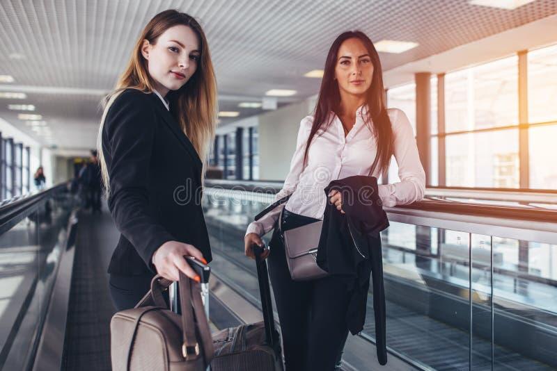 Zwei weibliche Teilhaber, die auf beweglichem Gehweg mit den Sandsäcken gehen zum Abfahrtaufenthaltsraum stehen stockbilder