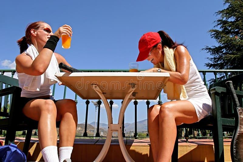 Zwei weibliche Tennisspieler, die einen Witz nach einem Spiel teilen. Genießen eines Glases Orangensaftes in der Sonne. lizenzfreie stockfotos