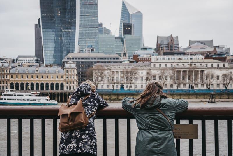 Zwei weibliche Touristen, welche die Themse, London, Großbritannien bereitstehen, auf dem Zaun sich lehnen und die Ansicht bewund lizenzfreie stockfotografie
