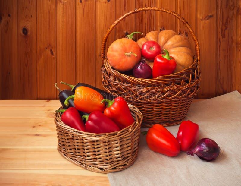 Zwei Weidenkörbe mit Frischgemüse auf Holztisch Herbstblattrand mit verschiedenem Gem?se auf wei?em Hintergrund lizenzfreie stockfotos