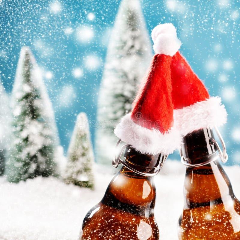 Zwei Weihnachtsbierflaschen klirren zusammen stockfotografie