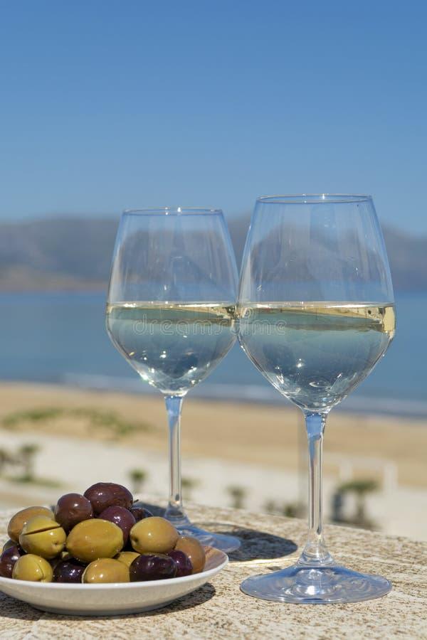 Zwei Weingläser mit dem Weißwein gedient mit Oliven auf Terrasse witn im Freien blauem Meer und Mountain View über Hintergrund stockbilder