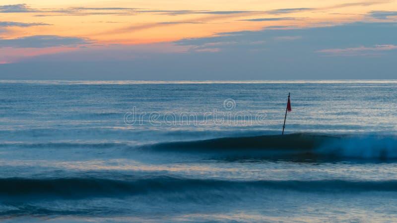 Zwei Wellen und eine rote Fahne stockfotografie