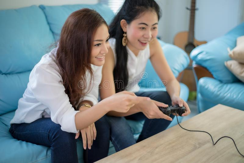 Zwei wettbewerbsfähige Freunde der Frauen, die Videospiele und aufgeregtes ha spielen stockfoto