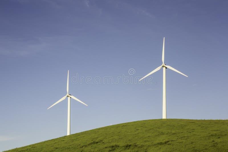 Zwei Windkraftanlagen auf einem Hügel stockfotos