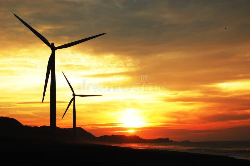 Zwei Windturbinen am Sonnenuntergang lizenzfreies stockfoto