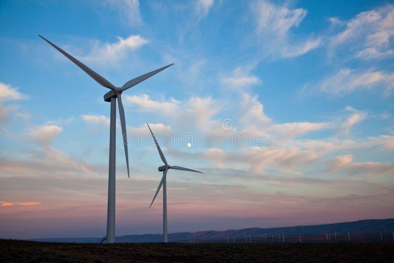 Zwei Windturbinen am Sonnenuntergang mit Mond stockfoto