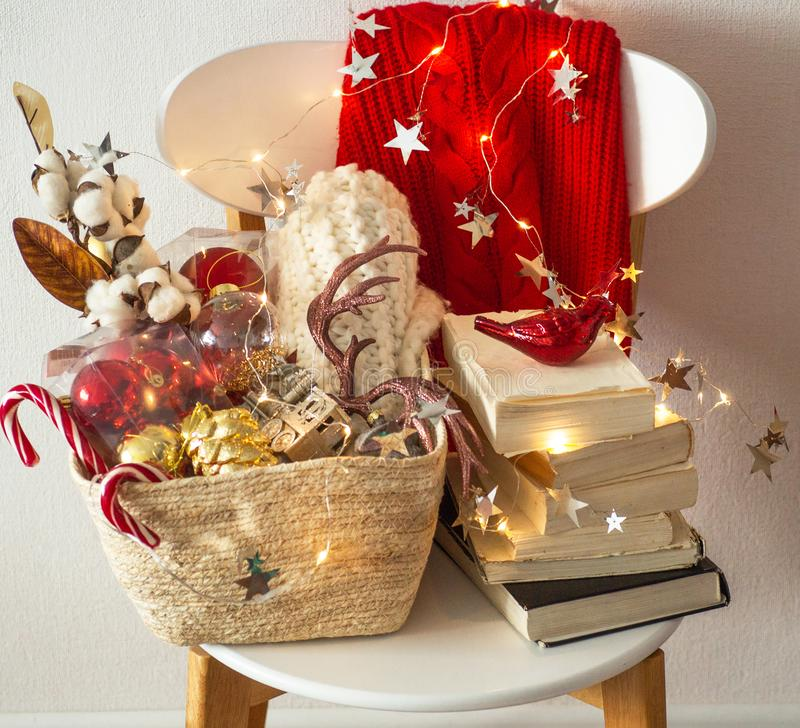 Zwei Winterstrickjacken gelegt auf einen Stuhl mit einem Korb von Weihnachtsdekorationen, Bücher, geführte Kettenlichter Winterle lizenzfreie stockfotografie