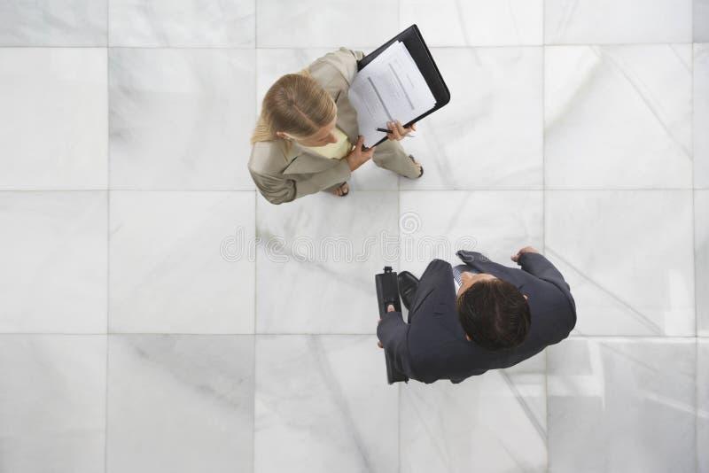 Zwei Wirtschaftler, die in der Lobby sich unterhalten stockfoto