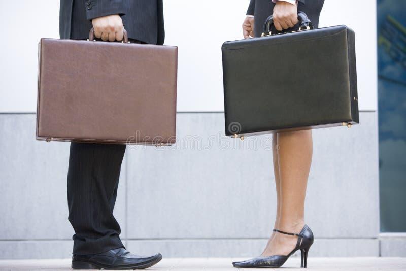 Zwei Wirtschaftler, die draußen Aktenkoffer anhalten stockbilder