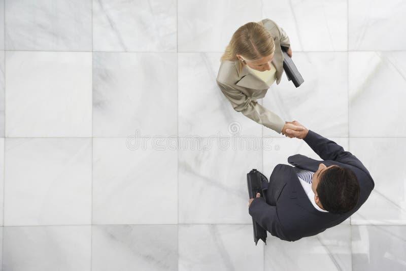 Zwei Wirtschaftler, die Hände in der Lobby rütteln stockbilder