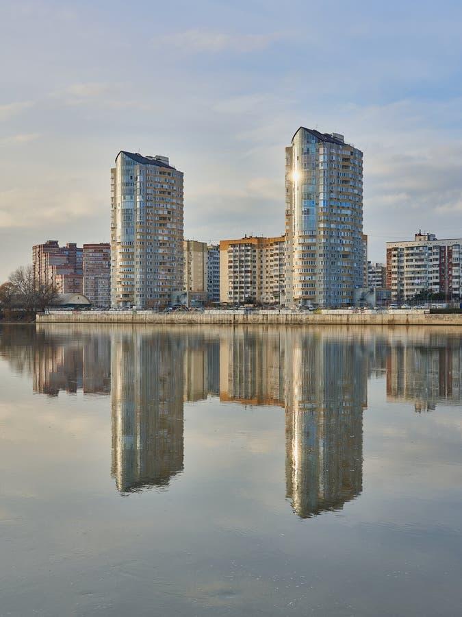 Zwei Wolkenkratzer auf dem Hintergrund der alten Stadt von Krasnodar Anfang Dezember werden im Kuban-Fluss bei Sonnenuntergang re stockfotografie