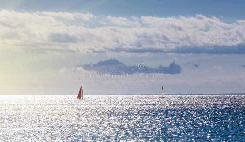 Zwei Yachten, die über den Ozean in der untergehenden Sonne segeln, strahlt aus stockfoto