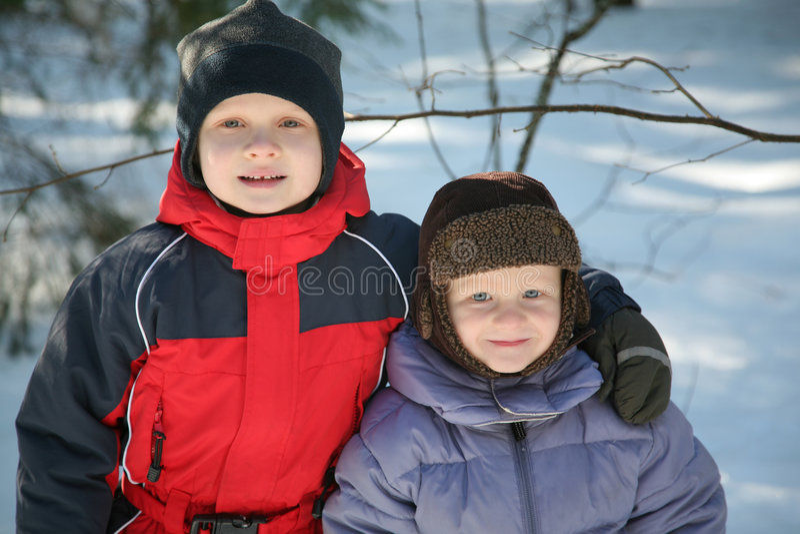 Zwei Young Boys, das im Schnee spielt lizenzfreie stockfotos