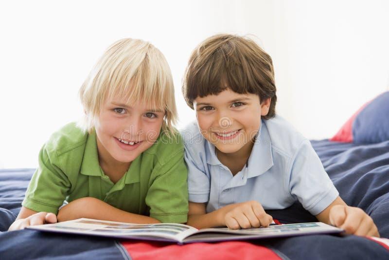 Zwei Young Boys, das sich auf einem Bett liest ein Buch hinlegt stockfoto