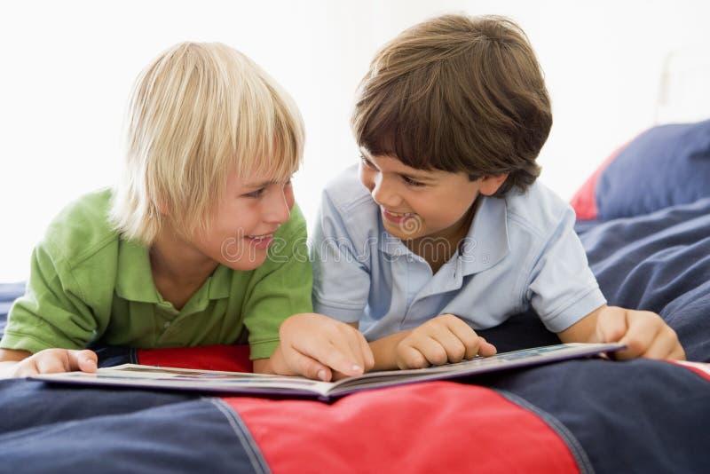 Zwei Young Boys, das sich auf einem Bett liest ein Buch hinlegt lizenzfreies stockfoto