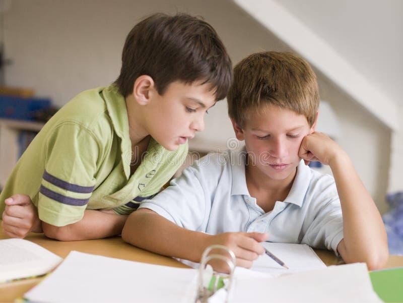Zwei Young Boys, das zusammen ihre Heimarbeit tut stockbilder