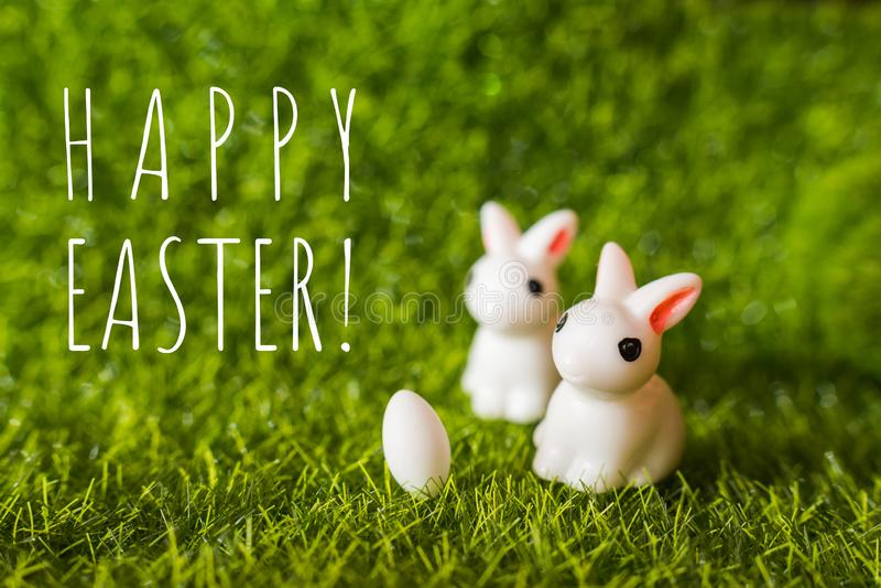 Zwei Zahlen eines Kaninchens und des Eies auf dem Gras stockbilder