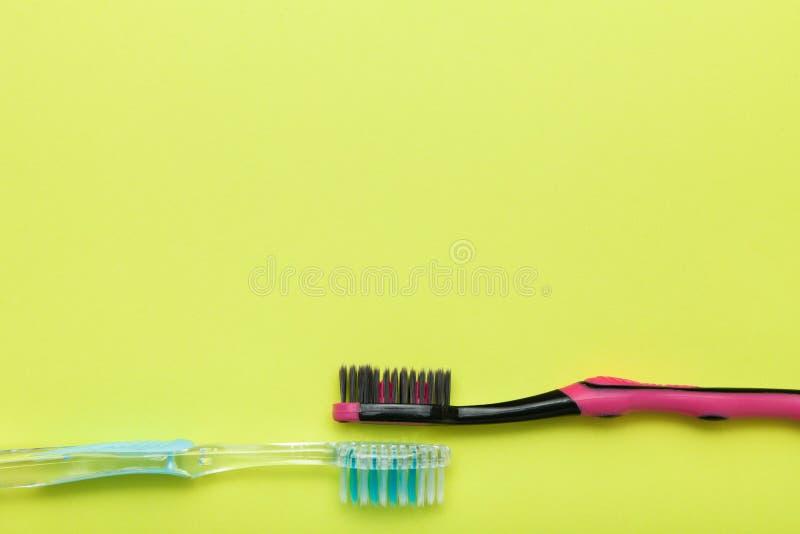 Zwei Zahnbürsten auf einem gelben Hintergrund Kopieren Sie Platz stockfotos