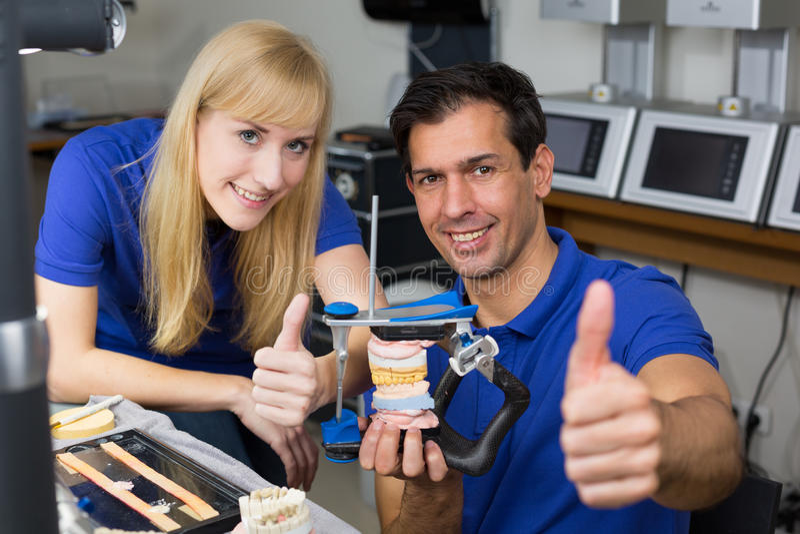 Zwei Zahntechniker mit dem Artikulator, der sich Daumen zeigt stockfotografie