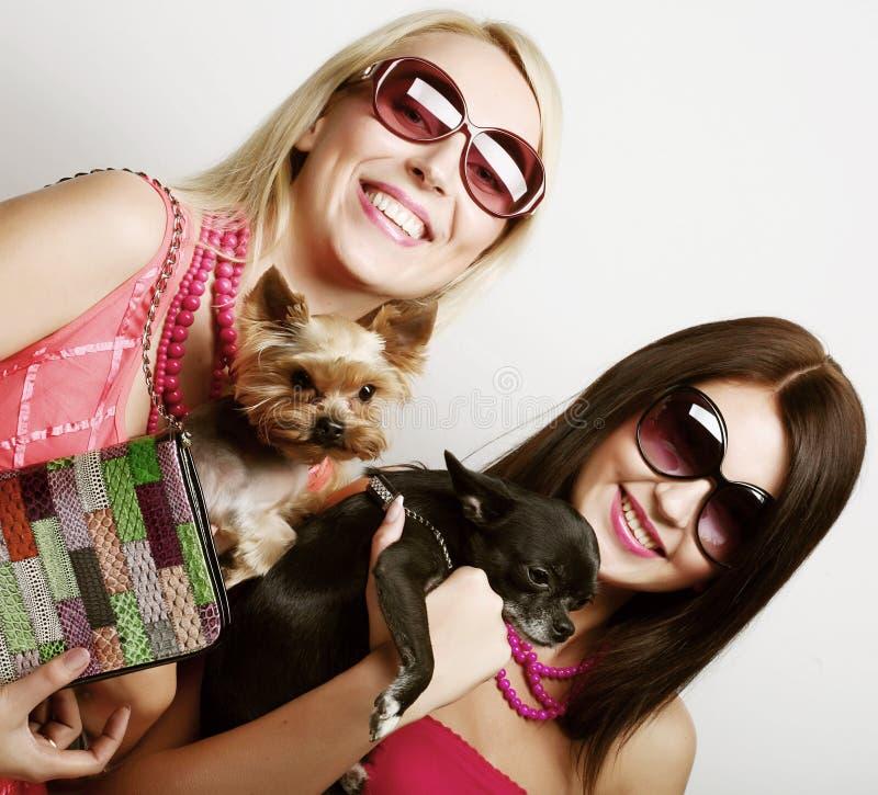 Zwei Zaubermädchen mit puppys lizenzfreie stockfotografie