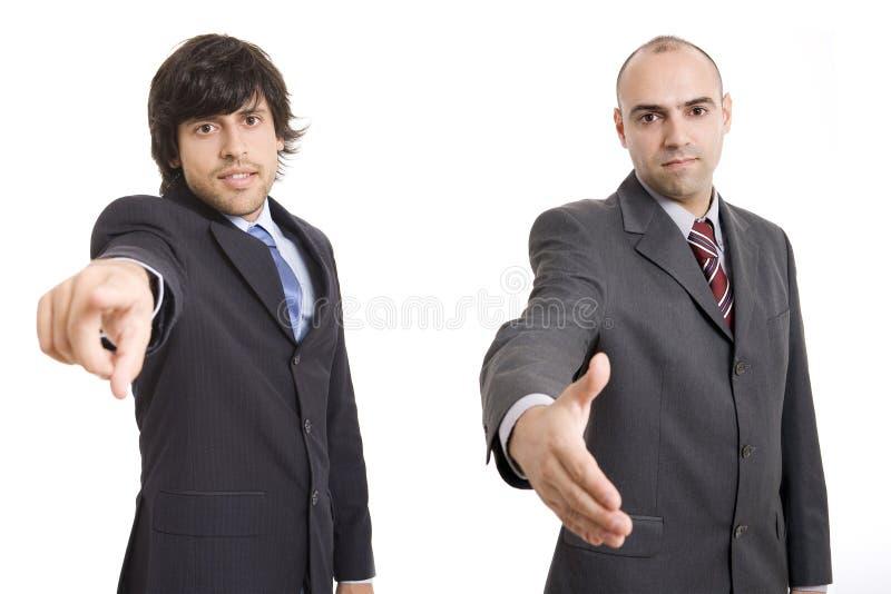 Zwei zeigende und rüttelnde Geschäftsmänner stockbild