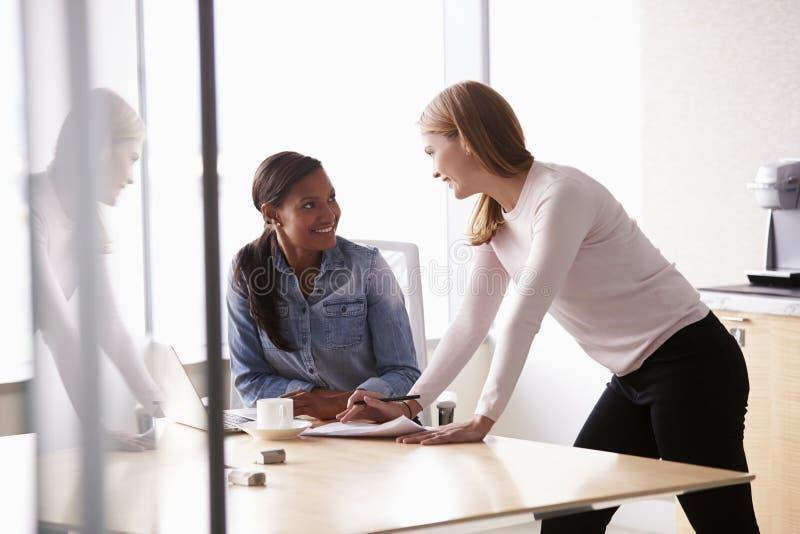 Zwei zufällig gekleidete Geschäftsfrauen, die im Büro arbeiten stockfotos