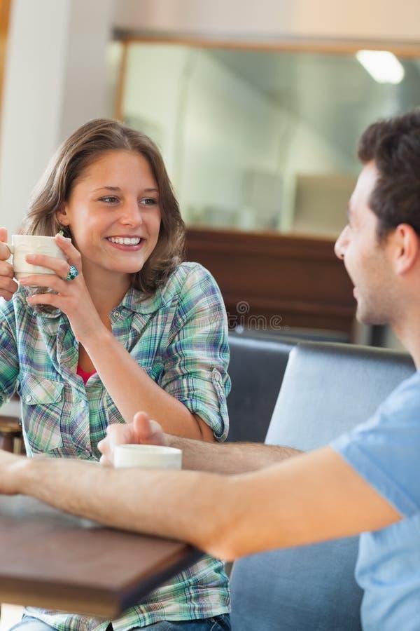 Zwei zufriedene Studenten, die einen Tasse Kaffee haben stockfotografie