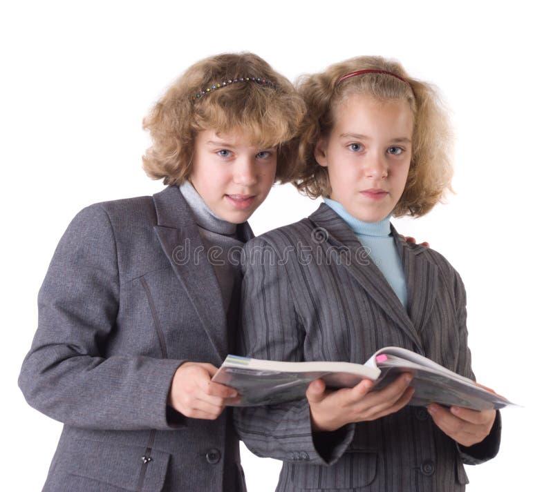 Zwei Zwillinge mit Lehrbuch stockbild