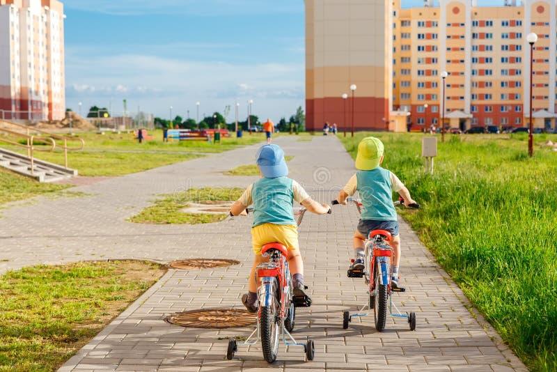 Zwei Zwillingsbrüder, die zusammen Fahrräder reiten lizenzfreie stockfotos