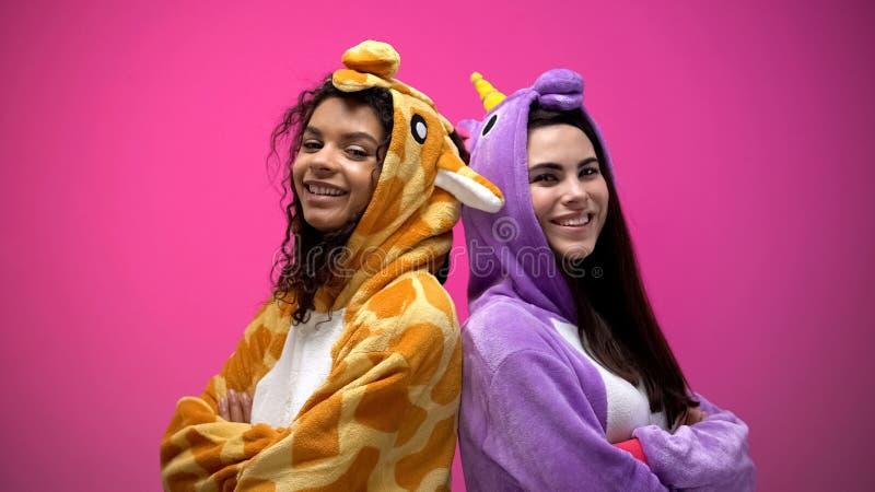 Zwei zwischen verschiedenen Rassen Frauen in den lustigen Pyjamas, die zurück zu Rückseite mit den Händen stehen, kreuzten stockfotos