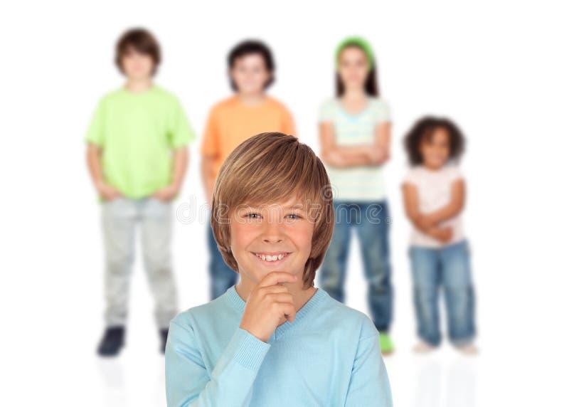 Zweifelhaft Jugendlichjunge mit anderen Kindern lizenzfreie stockbilder
