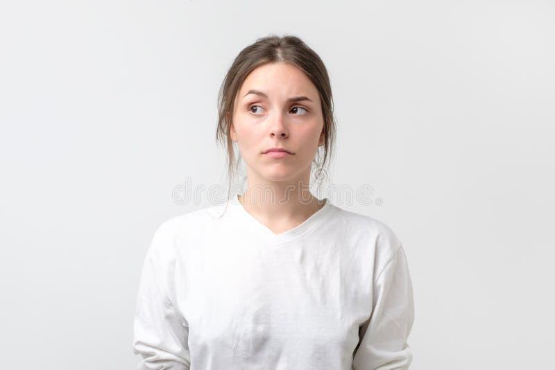 Zweifelhafte Frau, die mit Ungläubigkeitsausdruck beiseite schaut lizenzfreies stockfoto
