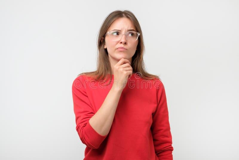 Zweifelhafte Frau, die mit Ungläubigkeitsausdruck beiseite schaut lizenzfreie stockfotos