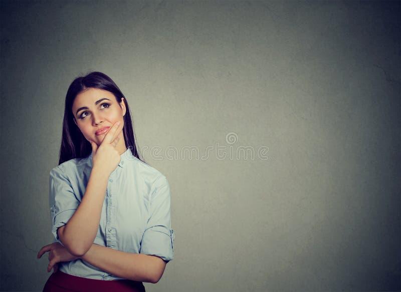 Zweifelhafte Frau, die oben in den Wundern schaut lizenzfreies stockbild