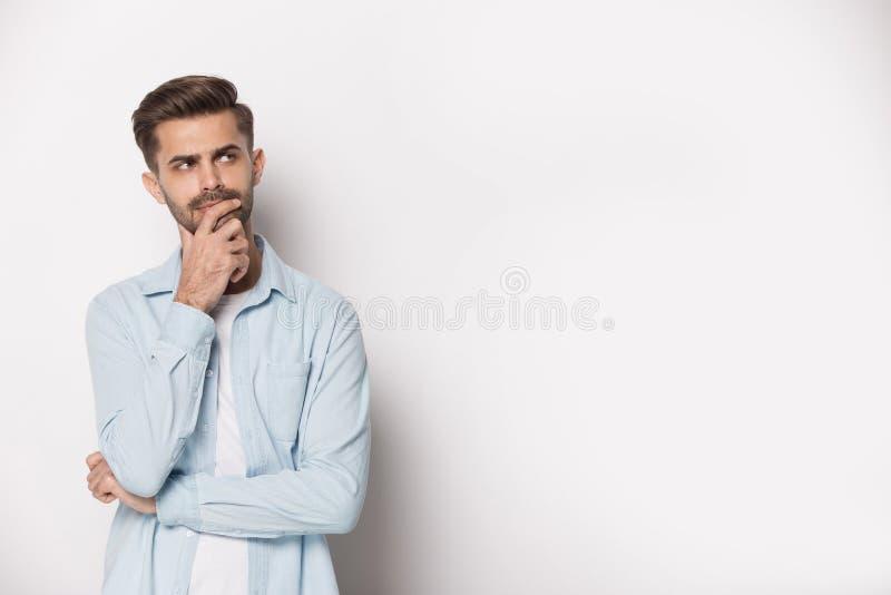 Zweifelhafte Haltung des nachdenklichen Kerlgefühls lokalisiert auf weißem Studiohintergrund stockfoto