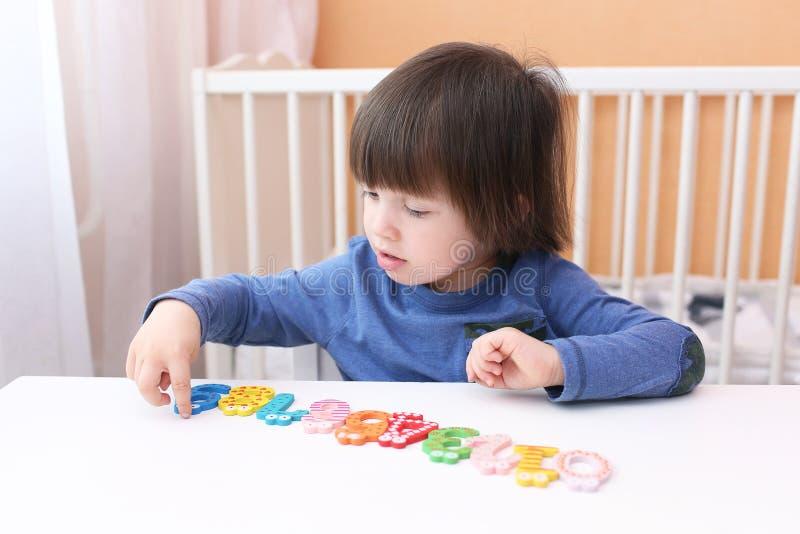 Zweijähriger Junge spielt die Zahlen stockbild