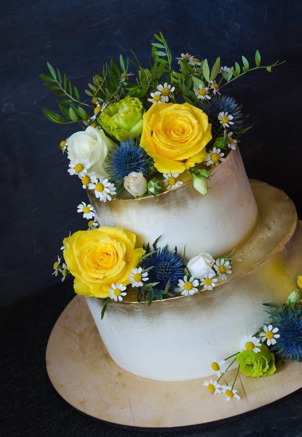 Zweischichtige vergoldete Hochzeitstorte mit Blumen stockfoto