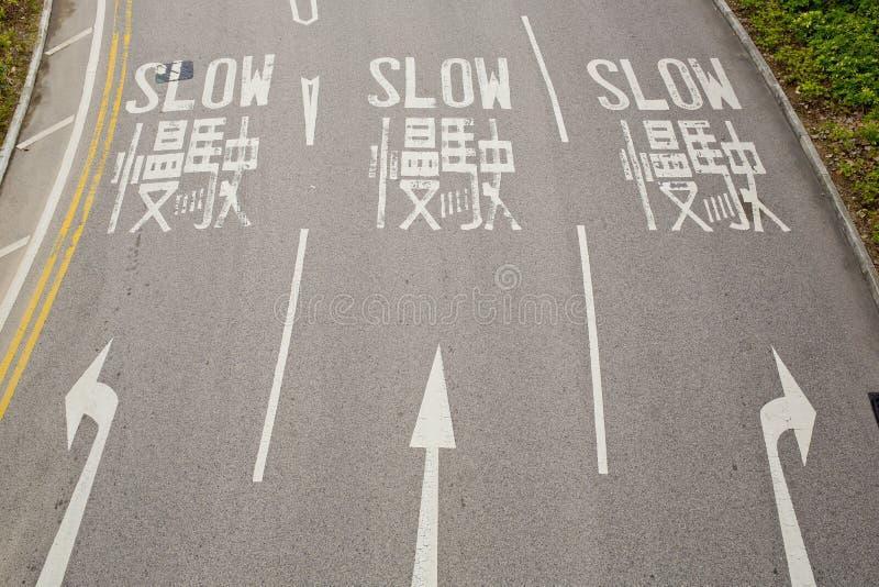 Zweisprachiges (englisch und chinesisch) langsames Verkehrsschild für Fahrer stockfoto