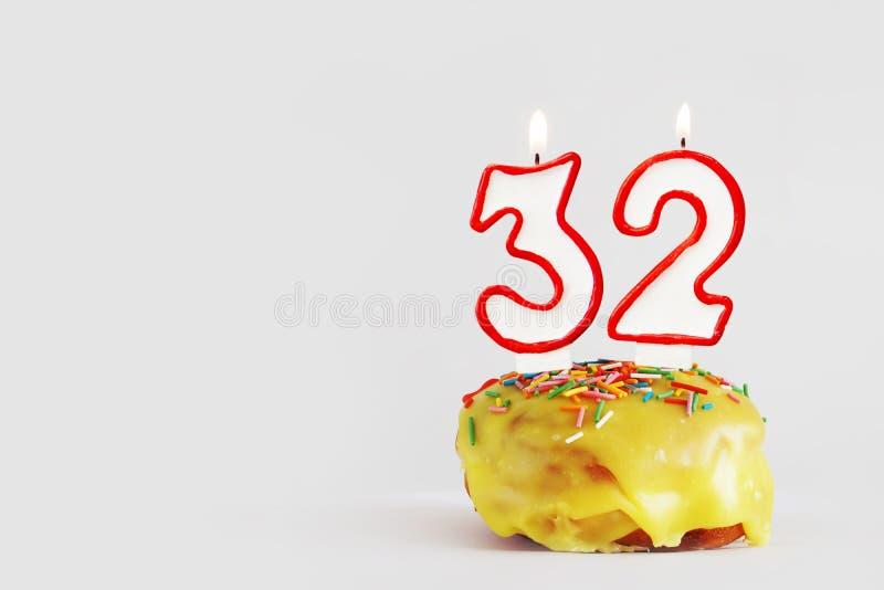 Zweiunddreißig Jahre Jahrestag Geburtstagskleiner kuchen mit weißen brennenden Kerzen mit roter Grenze in Form von Nr. zweiunddre lizenzfreies stockfoto