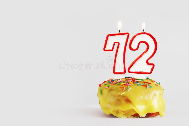Zweiundsiebzig Jahre Jahrestag Geburtstagskleiner kuchen mit weißen brennenden Kerzen mit roter Grenze in Form von Nr. 72 lizenzfreie stockfotografie