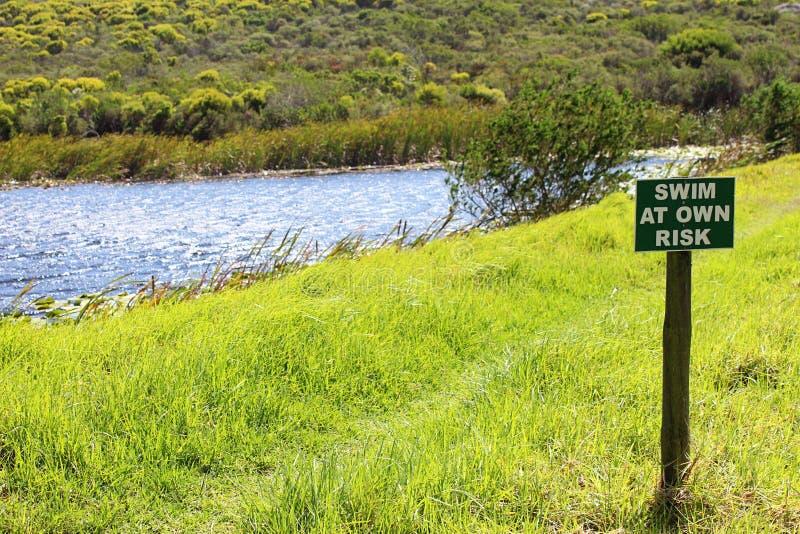 ` ZWEM OP EIGEN RISICO, leest ` een teken naast rivier stock afbeelding