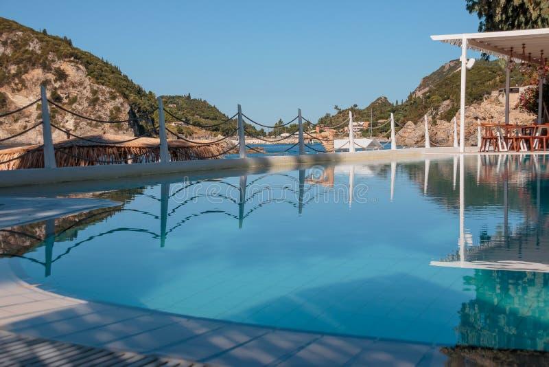 Zwembad bij luxevilla met een mening van berg en overzees bij mooie ochtend Leeg zwembadterras met stock afbeelding