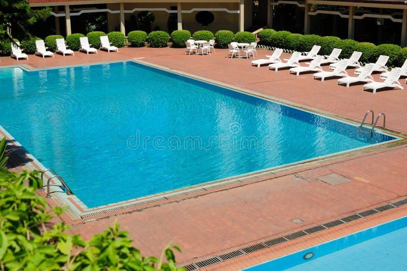 Zwembad en chaise-longues stock foto's